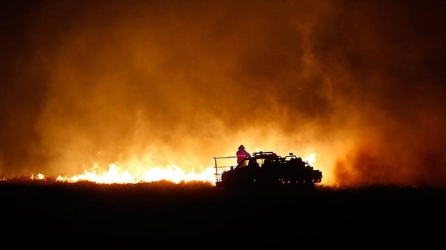 Firefighters from across Kansas and Oklahoma battle a wildfire near Protection, Kansas, Monday, March 6, 2017.