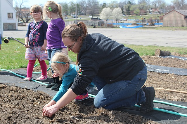 Parents Day Out instructor Chloe Flinn helps pre-schooler Ellie Fritz plant seeds in the community garden at First Baptist Church of Shawnee.