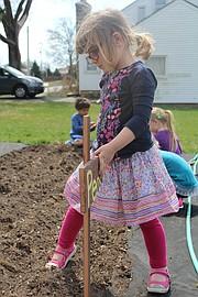 Garden organizer Katie Reimer's daughter, Marie, helps plant peas.