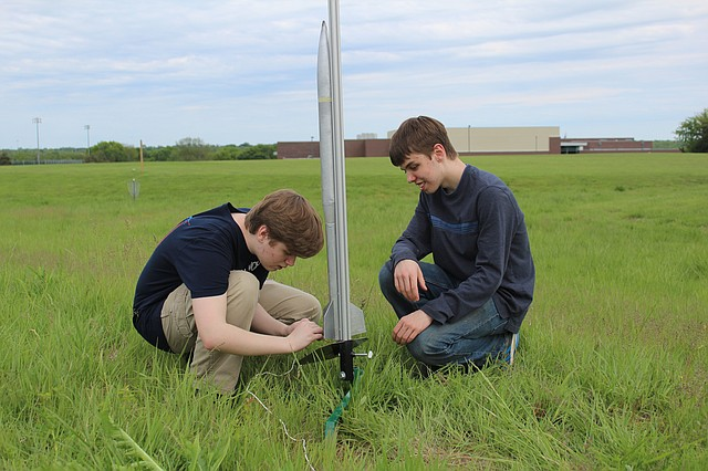 De Soto High School students Chad Manhart, left, and Zach Deibert, right, make sure the rocket is ready to launch.