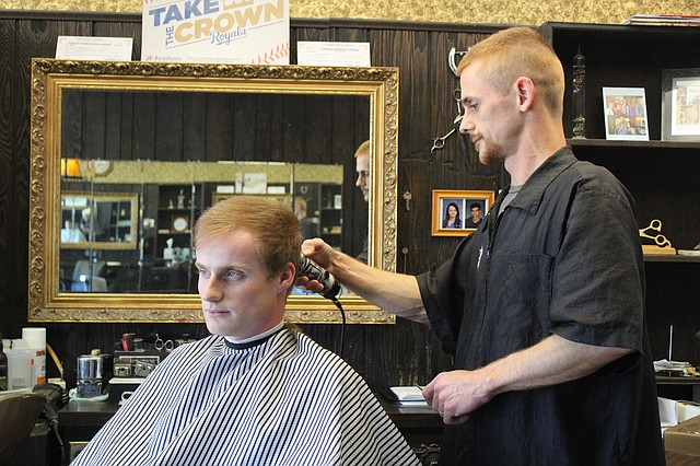 Gentlemen's West owner Andy Enyeart trims longtime customer Andrew Alvey's hair in the shop's current location near Nieman Road and Shawnee Mission Parkway. The shop will relocate down the street to Quivira Road this weekend.