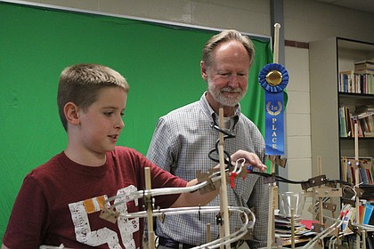 Broken Arrow Elementary School fourth-grader Owen Unruh demonstrates how to use the marble track, while club adviser Rich Maxwell observes.