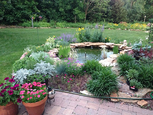 The Ezell Garden, sitting at a home in Enchanted Lake Estates, features a perennial-bordered goldfish pond.