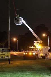 A Kansas City Power & Light linesman works to restore power near Midland Drive and Renner Road early Saturday morning.