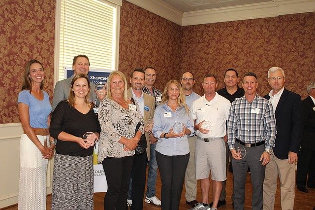 Mayor Michelle Distler, far left, poses with representatives from the majority of companies which won awards at the SEDC luncheon last week. Nine companies were given business development awards and two downtown businesses were also recognized.