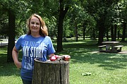Tammie Wagner stands with painted rocks in Tonganoxie VFW Park. Wagner recently started a Facebook group encouraging placing and finding painted rocks.