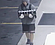 Second suspect wearing a backpack and carrying stolen merchandise, in front of ...