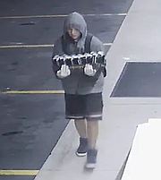 Second suspect wearing a backpack and carrying stolen merchandise, in front of the business.