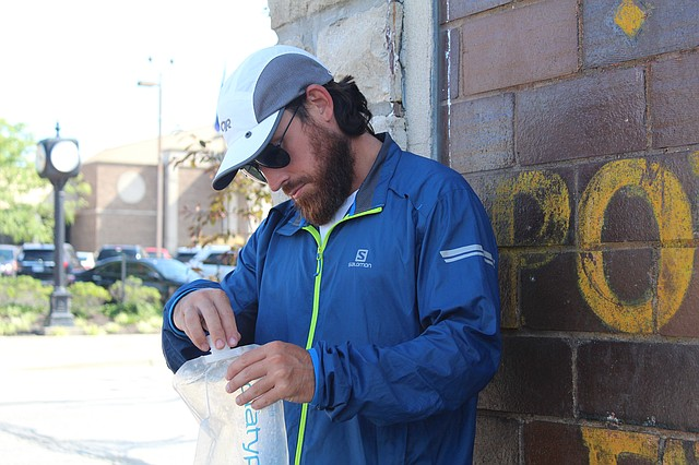 Frank Chiarelli, of Chicago, examines his water pouch in downtown Shawnee.