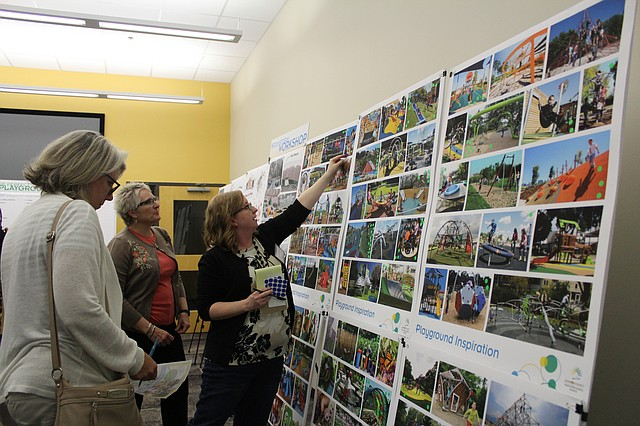 Residents study the inclusive playground inspiration boards at JCPRD's recent open house.
