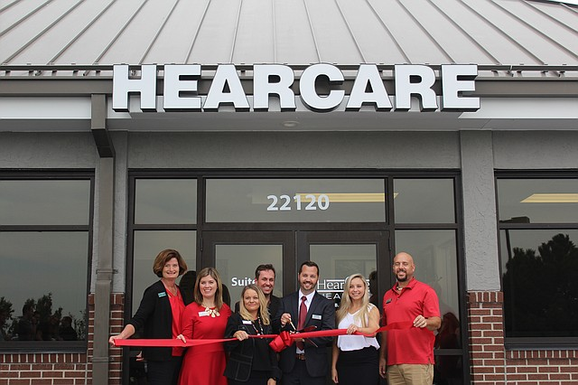 Employees and city officials pose at the HearCare Hearing ribbon cutting ceremony on Friday afternoon.