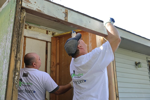Volunteers replace rotted wood from a small storage area on the back of a Shawnee house on Saturday morning. The project was a collaboration between the nonprofit organization Rebuilding Together Shawnee and communications company Spectrum.