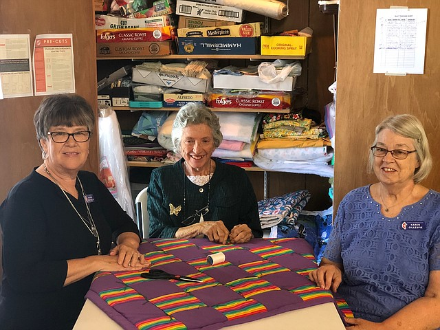Doing for Others group members Maxine Reynolds, Tacie Walser and Karen Gillespie gathered recently to put the finishing touches on a quilt they will give away.