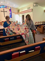 Church members Sandy Evans and Debbie Umbarger arrange quilts for the Nov. 4 Quilt Show.