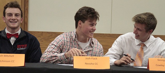 Shawnee Mission Northwest senior baseball players Josh Mitchell (left), Josh Flack (middle) and George Specht (right) all flash smiles after signing their national letters of intent on Wednesday.