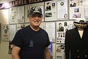 Former maintenance director Tom D'Andrea poses in front of the senior living center's veterans memorial.