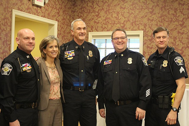Carol Gonzales, recently resigned Shawnee city manager, poses with a handful of Shawnee's finest at her goodbye reception. From left to right, the officers are Captain Jim Baker, Captain Mitch Brim, Major Sam Larson and Sergeant Jon Pirie.