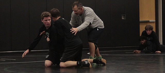 De Soto wrestling coach Shannon Sawner works with two of his wrestlers during practice on Nov. 15.
