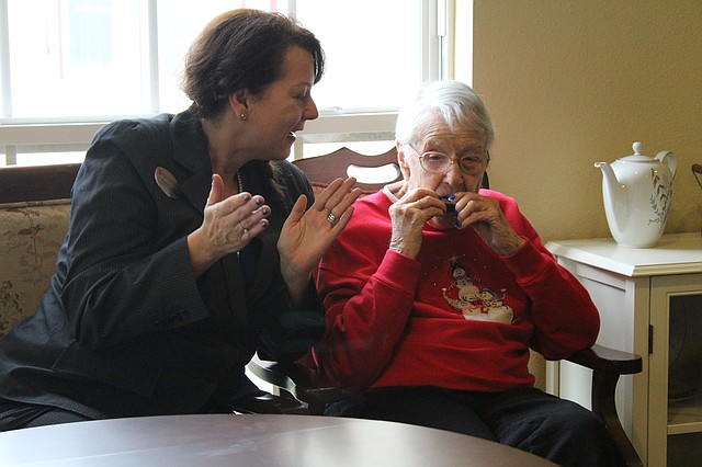 Dorothy Plummer, right, plays the harmonica at Brookdale College Square, while a staff member claps along.