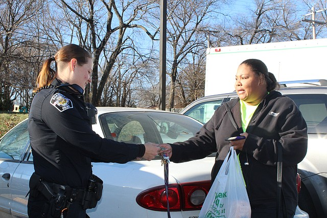 Shawnee police officer Crystal Herber hands a hundred-dollar bill to Lenexa mom Latoria Burden.