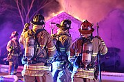 Overland Park Firefighters await an assignment on a house fire call in the 5000 block of Nieman Road early Friday.