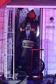 Firefighters douse a hotspot just inside the front door of the northeastern Shawnee home early Saturday.