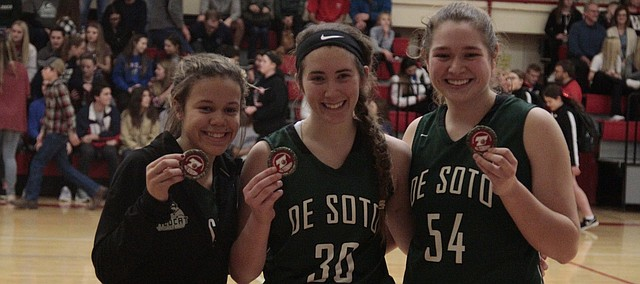 From left: LaMyah Ricks, Mackenzie Shupe and Emily Fuhr hold up their medals after being named to the Tonganoxie Invitational girls all-tournament team following the De Soto girls basketball team's loss to Jefferson West on Saturday.