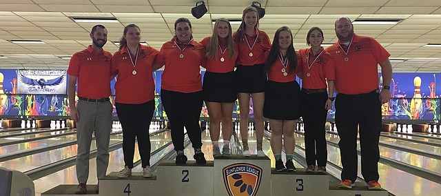 The Shawnee Mission Northwest girls bowling team stands on awards podium after its second-place finish at the Sunflower League meet on Tuesday at Mission Bowl 'N Olathe. Pictured from left: Assistant coach Justin Peterson, Emma Reinke, Cheyanne Bolin, Emilia Battles, Hadley Sayers, Alaina Burris, Charlie Queral and head coach Billy Dent.