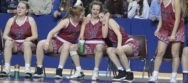 St. James senior Mary Goetz (22) shares a special moment with senior Claire Kearney (13) and sophomore Madi Biondo (1) in the closing seconds of the Thunder's 62-29 loss to Liberal in the quarterfinals of the Class 5A girls basketball state tournament on Thursday at the Kansas Expocentre in Topeka.