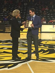 "Dispatch sports reporter Chris Duderstadt receives his ""Sportswriter of the Year"" plaque during an awards presentation at the Charles Koch Arena in Wichita on March 7."