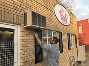Mike Ryan works on sprucing up the front of Ol' Doc's Pop Shop this past November in downtown Tonganoxie.