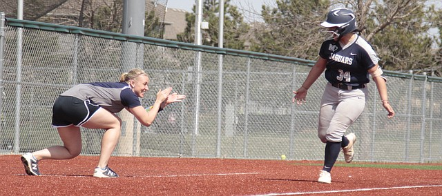 Mill Valley softball coach Jessica DeWild applauds Jess Garcia after her two-run home run in the seventh inning of the Jaguars' 6-4 win over Olathe East on Thursday at the College Boulevard Activity Center.
