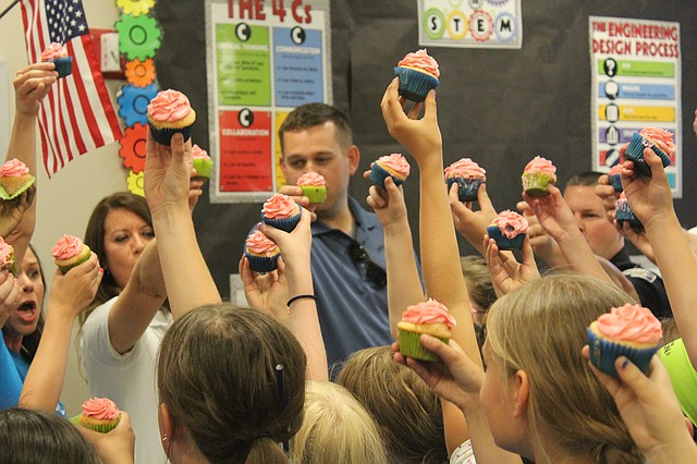 The Girls on the Run team at Clear Creek Elementary School in western Shawnee cheers after presenting first responders with homemade cupcakes.