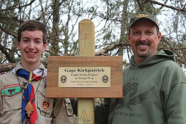 Gage Kirkpatrick, left, and his father, Rich, pose next to his engraved sign at the campsite he created for his Eagle Scout project.