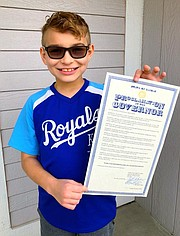 Eli Duby, a Clear Creek third grader, holds up a proclamation from the governor of Kansas declaring May as NF awareness month.