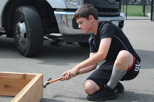 Caleb Herken-Borders helps construct a vegetable garden bed at Shawanoe Elementary School.