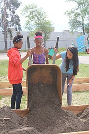From left to right, Shawanoe sixth graders Raven Hill, Ziarre Majeed and Dulce Rodriguez-Torres dump a wheelbarrow full of dirt into a garden bed on May 15.
