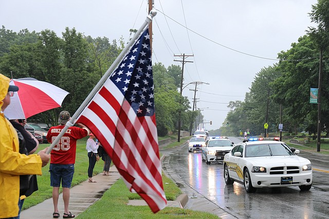 People line the streets of Shawnee to pay their respects to two fallen officers during a funeral procession last Thursday.