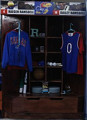 Lockers for Raegan and Bailey Ramsdell sit in the corner of a garage, which doubles as a mini Allen Fieldhouse, at their family's Shawnee residence. The lockers are designed like the ones for the KU basketball players in the Allen Fieldhouse locker room.