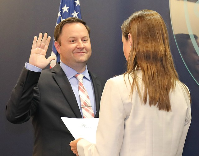New Shawnee city manager Nolan Sunderman gets sworn in by the mayor during a council meeting.