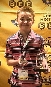 Mill Creek Middle School student Colton Martin poses with his plaque and trophy after making it to the quarterfinals round of the National History Bee in Atlanta.