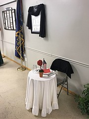 Black cloth is draped over the Tonganoxie VFW Post 9271 charter Thursday at the VFW Post Home in Tonganoxie. The black cloth and the set table were in honor of longtime VFW and community member Larry Meadows, who died July 21. The meal followed a service at the Tonganoxie Performing Arts Center and burial at Maple Grove Cemetery.