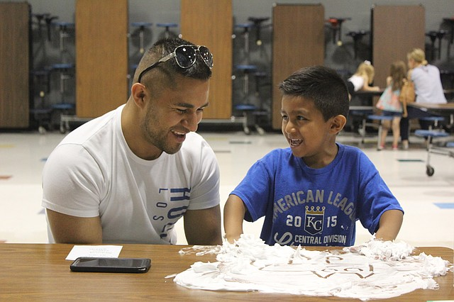 Eddie Penaloza and his son, Alexander, draw images in shaving cream during the parent engagement session of Jump Start for Learning at Bluejacket-Flint Elementary School.