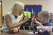 Leigh Anne Neal, Shawnee Mission associate superintendent of early childhood education, goes over numbers with future Bluejacket-Flint kindergartner Kolton Long.
