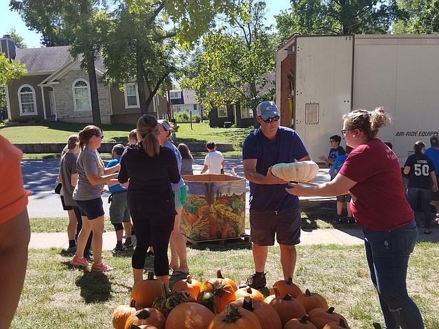 Community volunteers help unload pumpkins at Shawnee United Methodist Church on Sunday.