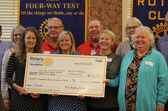 Grant recipients pose with a giant check at the Rotary Club of Shawnee meeting on Friday morning. Five non-profit organizations received grant money, which was raised from A Taste of Shawnee and the Bike Safety Rodeo.