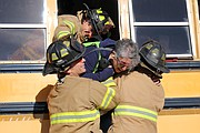 A volunteer plays the role of a hysterical passenger as firefighters lift her from the school bus.