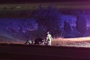 Firefighters and a police officer inspect the crashed motorcycle after the injured rider was loaded into an ambulance for transport to an area hospital.