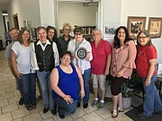 Local residents gather with WenDee Rowe and Mari Penner of the Kansas Sampler Foundation for a surprise We Kan! award presentation to Keyta Kelly on Thursday at Kelly Law Office.