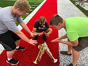 "Tonganoxie High School band members, from left, Ryan Black, Hayden Heyward and Hunter Calovich create a ""campfire"" of trumpets during band camp. Other members of the trumpet section followed suit. It was a particuarly warm day when they made their trucket campfires. They joked that it was cold and they needed to warm up by the fire."